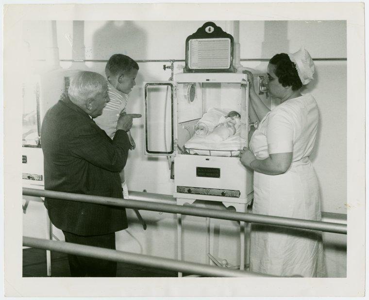 Dr. Martin Couney držící malého kluka se svou dcerou Hildegardou koukají do inkubátoru na výstavě New York World's Fair (1937).